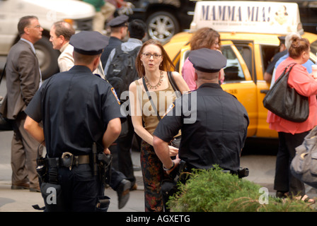 Woman asks police officers a question outside New York s Pennsylvania Station - Stock Photo