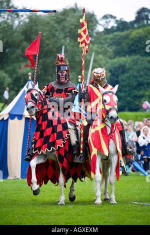 Medieval knights on horseback holding lance during reenactment tournament - Stock Photo