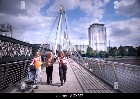 Three women with a baby walking on a bridge, Golden Jubilee Bridges, Thames River, London, England - Stock Photo