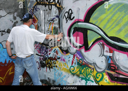 Man spraying graffiti on a wall - Stock Photo