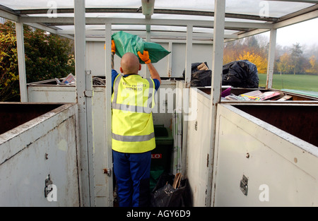 Council worker sorting rubbish for recycling in the collection lorry - Stock Photo