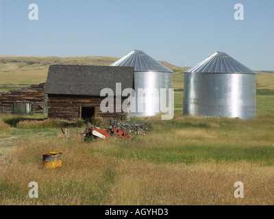 Metal Storage Silos Next to Old Log Cabin - Stock Photo