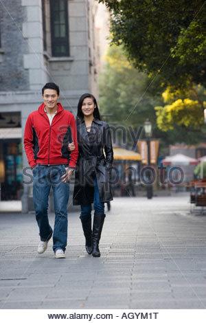 Young couple walking down urban street - Stock Photo