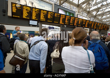 Commuters delayed on concourse watching timetable at Waterloo Station London - Stock Photo