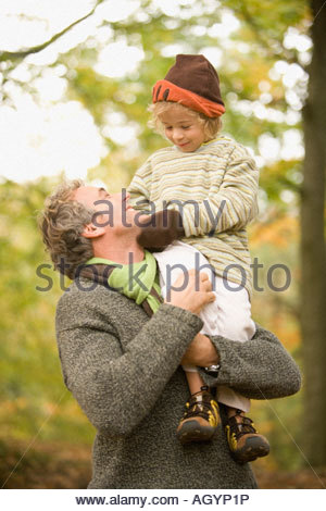Father carrying child on shoulders in the woods - Stock Photo