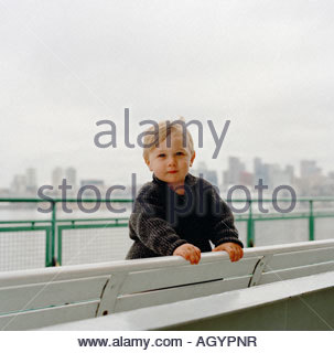 Young boy on bench on ferry - Stock Photo