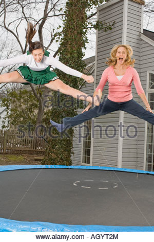 Cheerleader and mother jumping on trampoline - Stock Photo