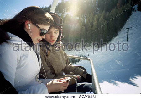Teenagers using mp3 players on ski lift - Stock Photo