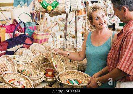 Mature woman with a senior man looking at each other and holding wicker baskets - Stock Photo