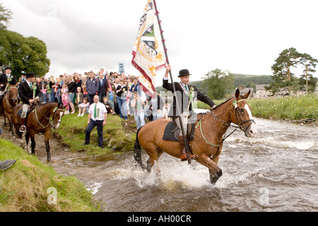 Riding the boudaries of the common land Langholm Common Riding Cornet with town standard crossing Ewes Water Scotland - Stock Photo