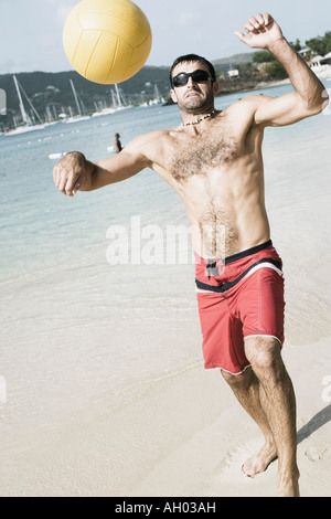 Mid adult man playing beach volleyball on the beach - Stock Photo