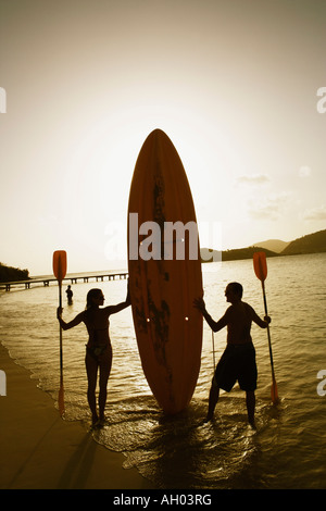 Silhouette of a man and a woman holding oars and a surfboard on the beach - Stock Photo