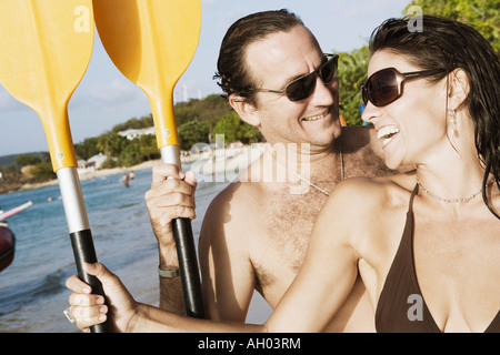 Close-up of a mid adult couple holding oars on the beach - Stock Photo