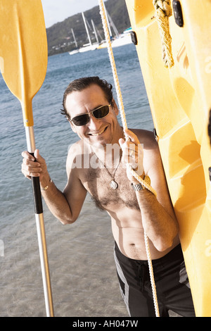Mid adult man standing with an oar and a surfboard on the beach - Stock Photo