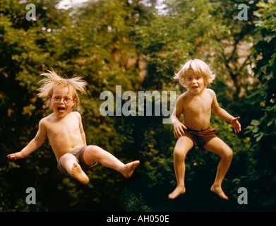 The trampoline is out of sight as two boys bounce - Stock Photo