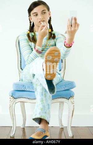 Girl sitting in chair, putting on make-up - Stock Photo