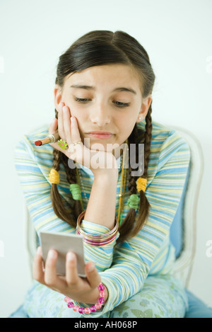 Girl looking at self in hand mirror, frowning - Stock Photo