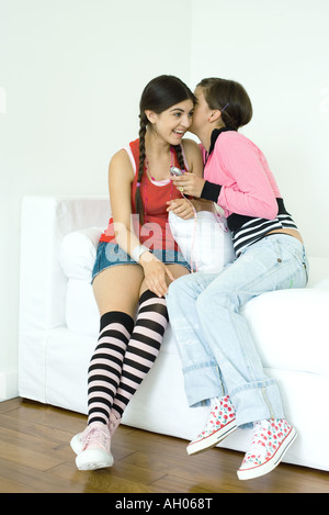 Two young female friends sitting on sofa, one whispering to the other - Stock Photo