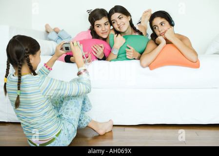 Three young female friends lying with heads on cushions while fourth friend takes photo - Stock Photo