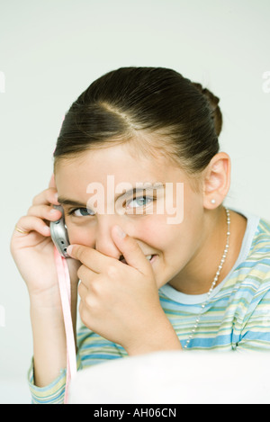 Girl talking on cell phone, covering mouth and giggling - Stock Photo