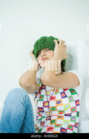 Teen girl wearing hat and headphones, eyes closed and hands over ears - Stock Photo