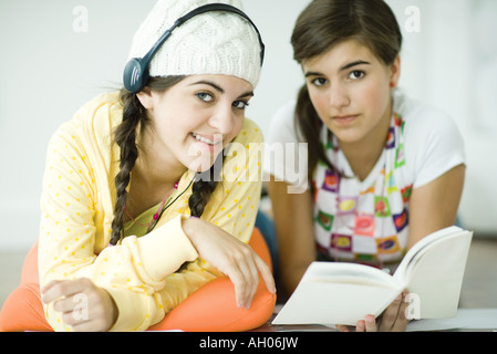 Two young female friends lying on floor, doing homework together - Stock Photo