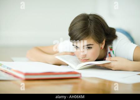 Teen girl lying on floor, doing homework - Stock Photo