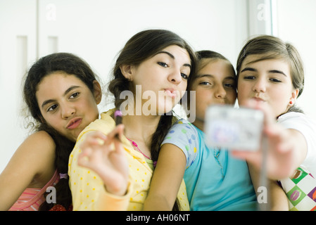 Young female friends with make-up looking at selves in hand mirror - Stock Photo