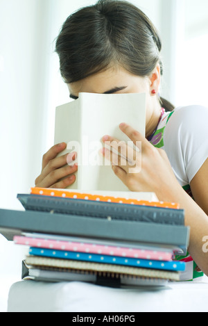 Teen girl with stack of homework, hiding face behind book, portrait - Stock Photo