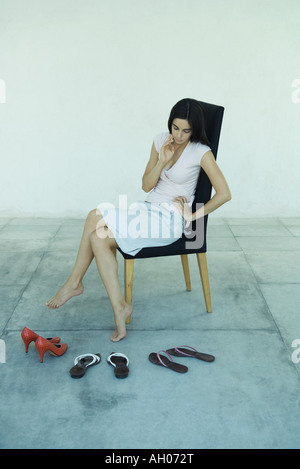 Young woman sitting in chair, looking down at three pairs of shoes, full length portrait - Stock Photo