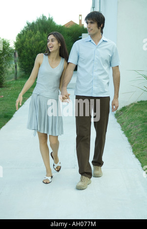 Young couple holding hands as they walk down sidewalk, looking out of frame - Stock Photo