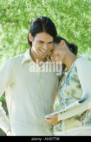 Couple standing outdoors holding newspaper, woman resting head on man's shoulder - Stock Photo