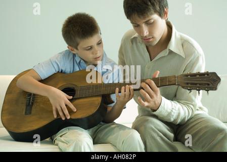 Man teaching boy to play the guitar