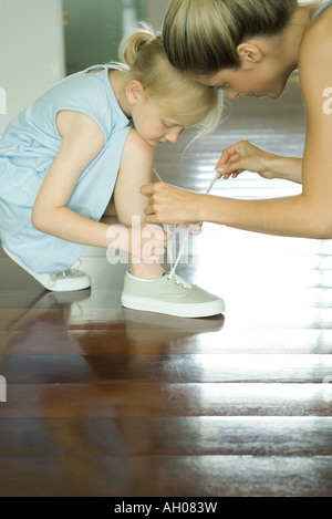 Mother helping little girl tie shoe laces - Stock Photo