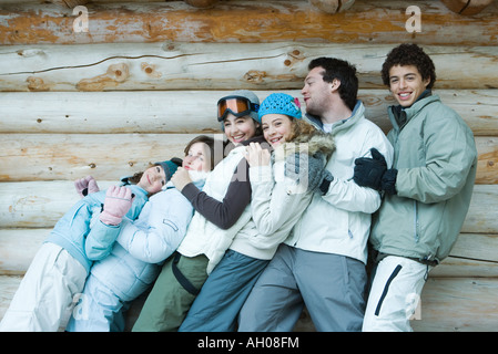 Group in winter clothes falling back onto each other, three quarter length, in front of log wall, portrait - Stock Photo