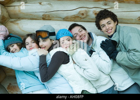 Group in winter clothes, leaning against each other, waist up, portrait - Stock Photo
