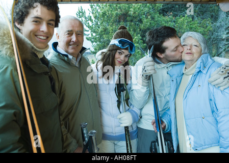 Group of skiers, young man kissing senior woman on check, portrait - Stock Photo