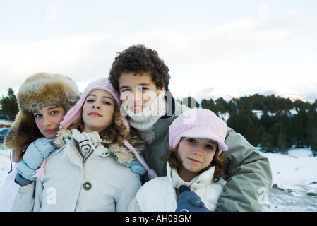 Group of young friends standing in snowy landscape, waist up, portrait - Stock Photo