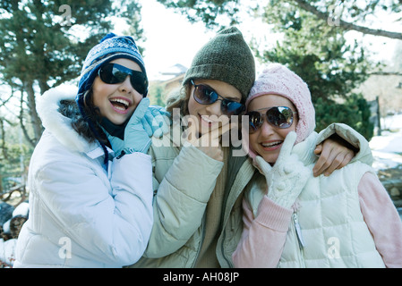 Three teen girls wearing winter clothes and sunglasses, holding chins, laughing - Stock Photo