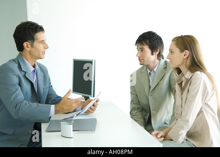 Young couple sitting across desk from businessman, businessman holding document and speaking - Stock Photo