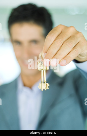 Real estate agent holding up keys, focus on keys in foreground, close-up