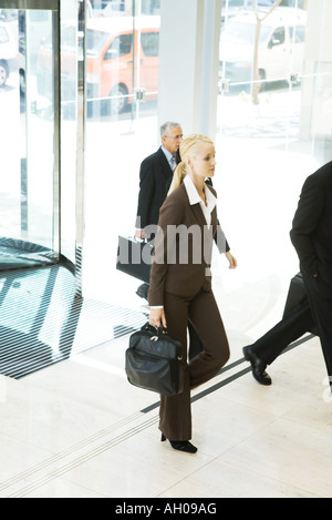 Young businesswoman entering lobby, carrying briefcase, man in background - Stock Photo