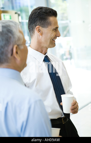Business associates smiling, holding hot beverages, side view - Stock Photo