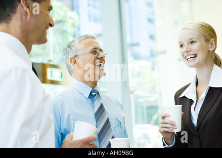 Business associates laughing together, holding hot beverages - Stock Photo