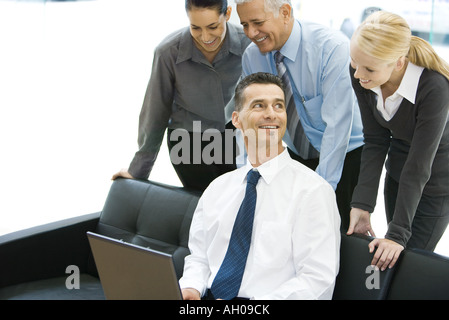 Businessman using laptop computer, smiling, associates looking over his shoulder - Stock Photo