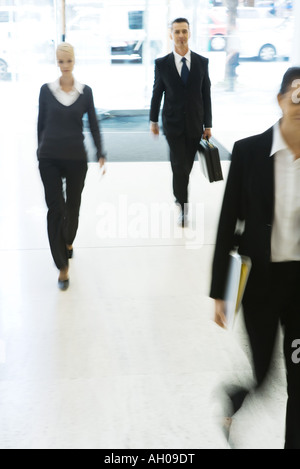 Business professionals walking in lobby, full length, blurred motion - Stock Photo