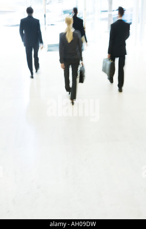 Business associates exiting lobby, rear view, blurred motion - Stock Photo