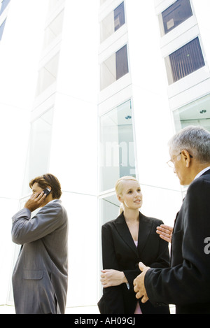 Two business associates standing, discussing, man using cell phone in background - Stock Photo