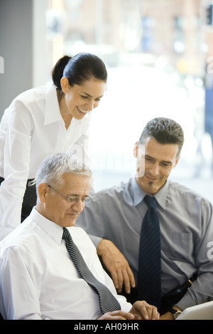Mature businessman using laptop computer, two colleagues looking over his shoulder - Stock Photo