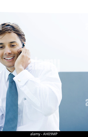 Young businessman using cell phone, smiling, cropped view - Stock Photo